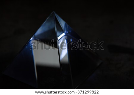 Glass prism in the dark with slight light refracting in the polished glass surface. Refractions of light in a glass prism. Focus is on front edge. Shallow depth of field.  - stock photo