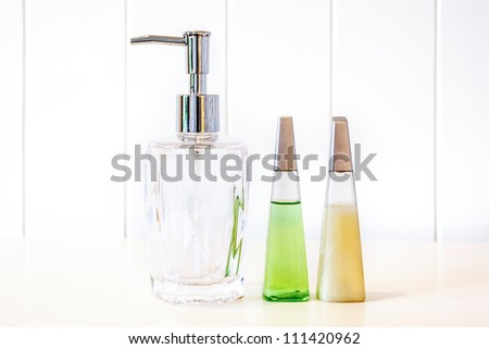 Glass pump soap bottle without label on white background - stock photo