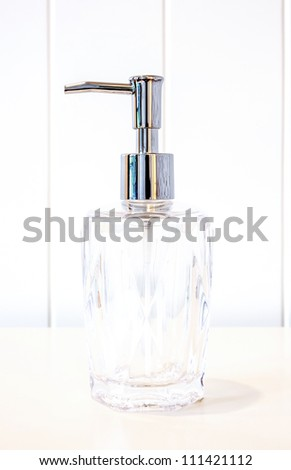 Glass pump soap bottle without label on white background