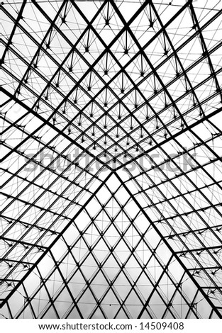 Glass pyramid entrance to the Louvre museum in Paris. Shot form the entrance floor up to the sky. - stock photo
