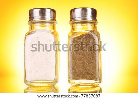 Glass salt and pepper shakers  on yellow background