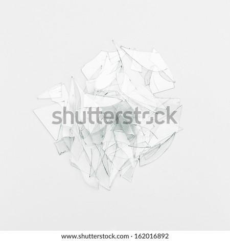 glass shards Broken window heap on white gray background - stock photo
