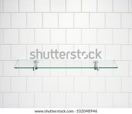 Glass shelf on white wall. - stock photo