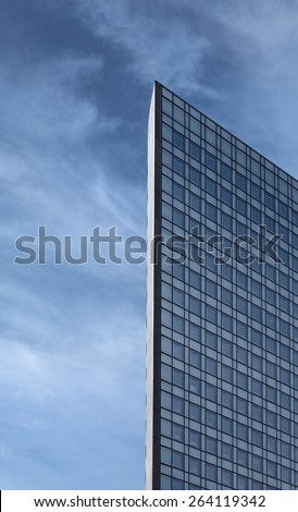 Glass Skyscraper with clouds and blue sky in background. Side profile of the building. - stock photo