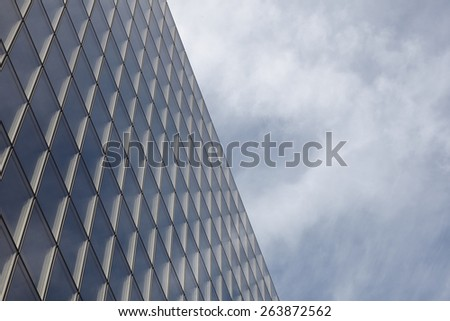 Glass Skyscraper with clouds in background. - stock photo