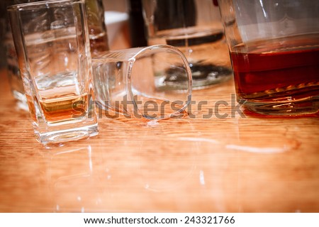 Glass, spilled whiskey and empty bottles on the bar. Abuse of alcohol hangover. Alcoholism concept. Drunk driver concept - stock photo
