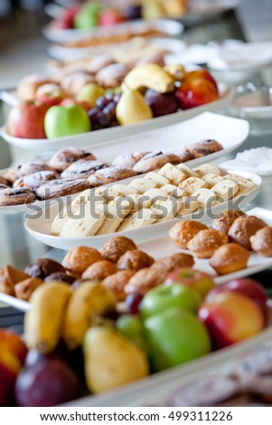 glass table covered with white plates with fruits and pastries