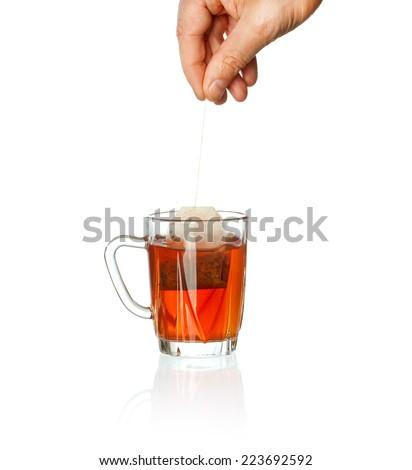 Glass teacup and hand holding tea bag - stock photo