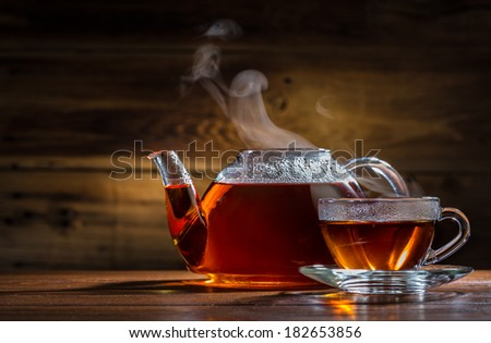 glass teapot and mug on the wooden background - stock photo