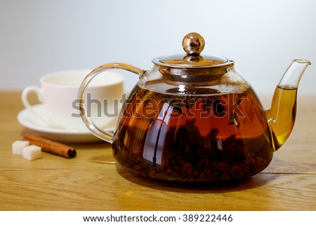 Glass teapot of invigorating fresh aromatic tea, classic white cup with saucer, sugar and cinnamon on a wooden table background.  - stock photo