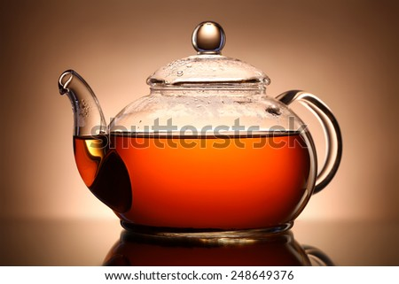 Glass teapot on brown background - stock photo