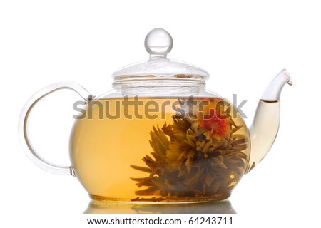 Glass teapot with blooming flower green tea on white background - stock photo