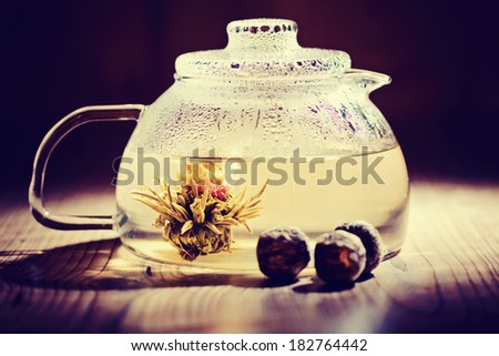 Glass teapot with blooming tea flower inside against wooden back