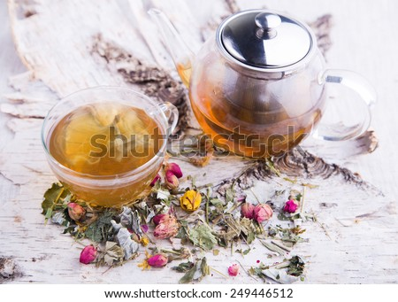 Glass teapot with cup of hot herbal tea with dry roses on tree white bark