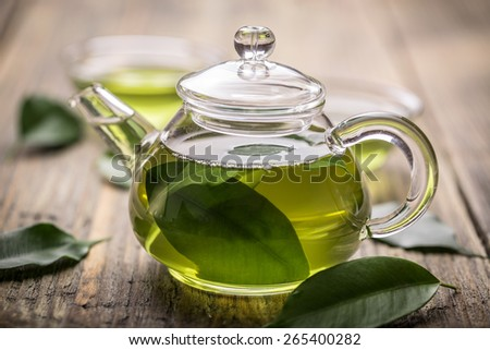 Glass teapot with green tea on wooden table - stock photo