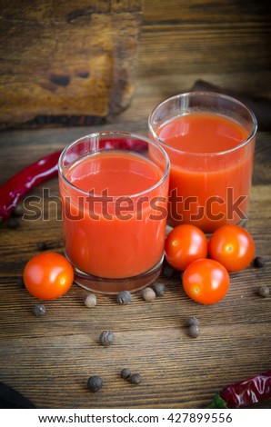 glass tomato juice pepper on a brown wooden background with pepper and cherry - stock photo