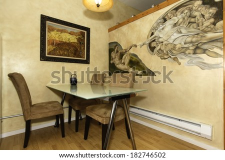 Glass top dining table with chairs. View of beautiful painted wall mural. Michelangelo work  - Creation of Adam. - stock photo