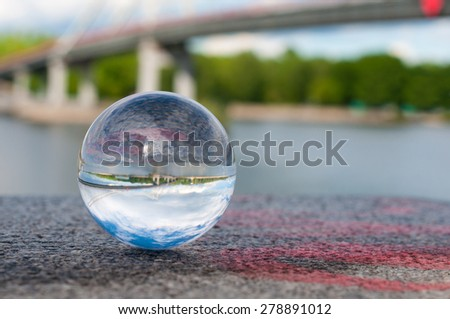 Glass transparent ball on bridger background and grainy surface. Texture, outdoors - stock photo