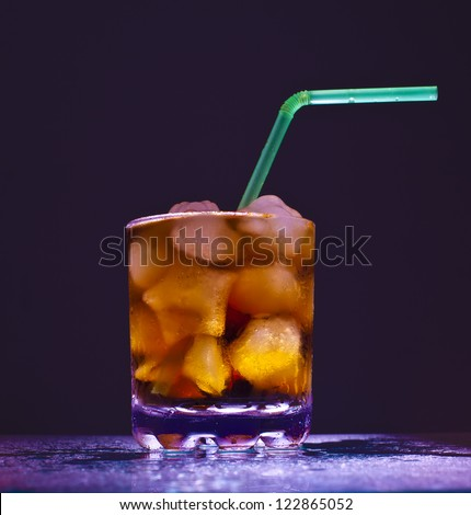 glass transparent glass with ice cubes and Coke with a green tube on blue background Space for inscriptions - stock photo