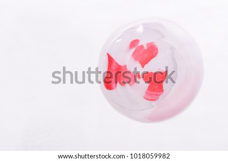 Glass tumbler with three red paper hearts under it staying on white fabric.