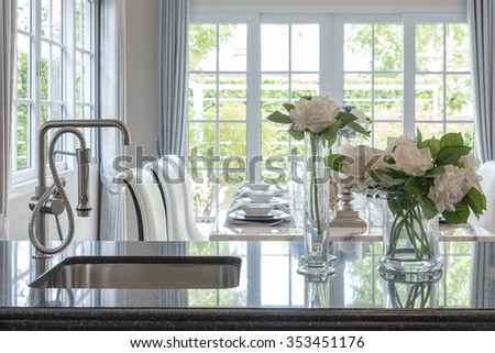 glass vase of flower on black granite counter with modern sink and faucet in classic pantry room