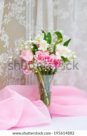 Glass vase with flowers as decoration on table - stock photo