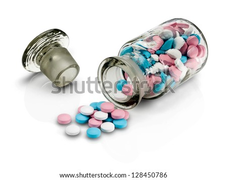 Glass vial with a glass stopper and group a pill on a white background