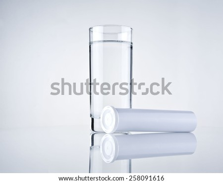 glass water and blank medicine container - stock photo