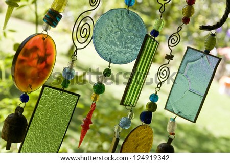 Glass wind chime hanging outside, shallow focus - stock photo