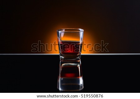 Glass with  alcoholic drink on a reflective background