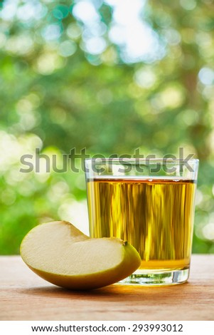 Glass with apple juice and apple lobule on the wooden table on green blurred background