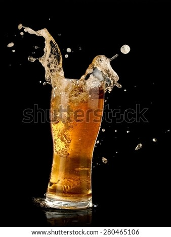 Glass with beer splash on black background - stock photo