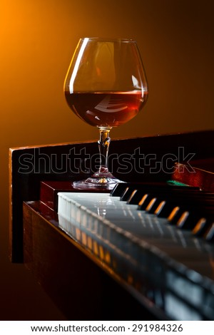 glass with brandy on a old piano - stock photo