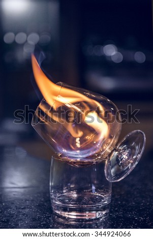 Glass with burning alcohol. Image of two glasses of burning emerald absinthe. Glass of tequila and flames - stock photo