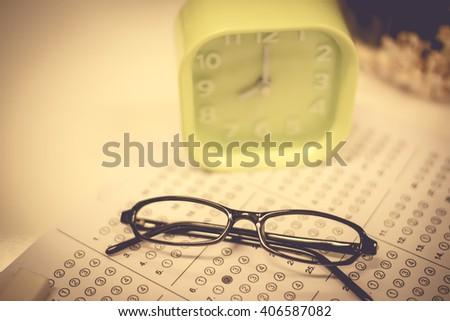 Glass with clock in exam concept.