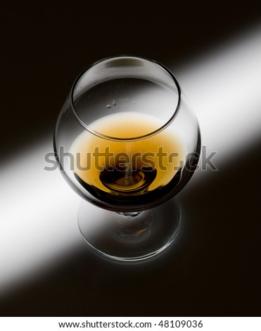 Glass with cognac on creative black background