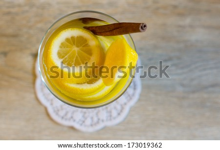 Glass with cut lemon fruit and water