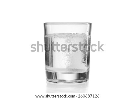 Glass with efervescent tablet in water. Isolated on white. - stock photo