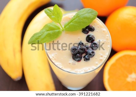 Glass with fresh blended smoothie with banana, orange and blueberries fruits with fresh mint leafs