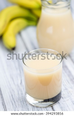 Glass with fresh made Banana juice (selective focus) on an old wooden table