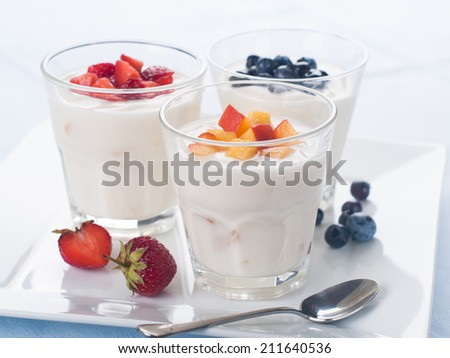 Glass with fruit and berry yogurt , selective focus - stock photo