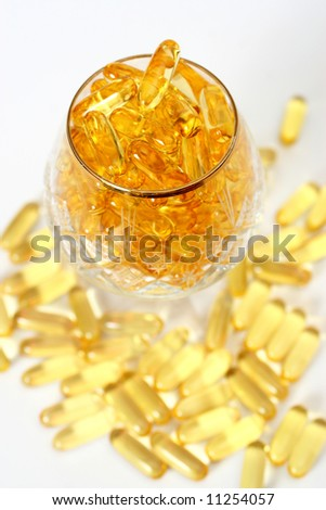 Glass with gold shiny boluses - stock photo