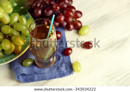 Glass with grape juice on blue napkin - stock photo