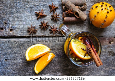 Glass with hot spiced wine with orange fruit, scarf and snow - stock photo