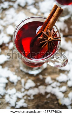 Glass with hot spiced wine with orange fruit, scarf and snow