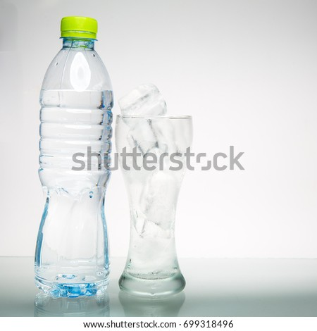 Glass with ice cubes and drink bottle. on white background