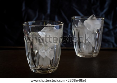 Glass with ice cubes. image dark tone - stock photo