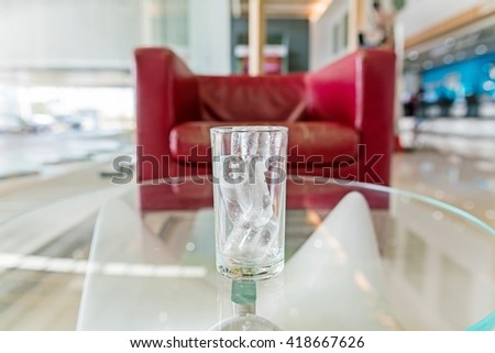 glass with ice cubes on a glass table and blurry red sofa background  - stock photo