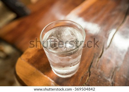 Glass with ice cubes on wooden table - Glass of very cold water ( top view )  - stock photo