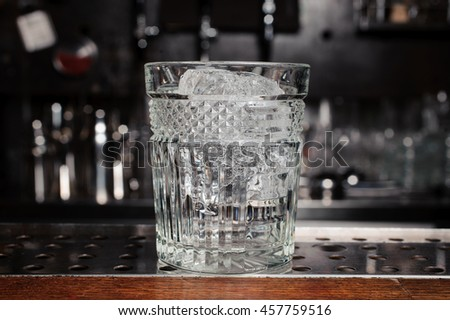 glass with ice on the bar - stock photo